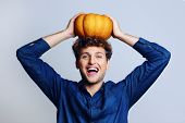 Portrait of a laughing man with pumpkin on head