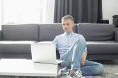 Full-length of man using laptop in living room