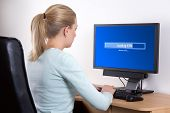 Back View Of Woman Using Personal Computer In Office