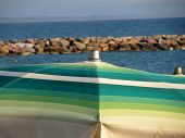 stock photo of leghorn  - Beach umbrella on sea background - JPG