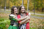 Two Young beautiful women, on yellow background autumn nature