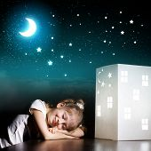 Little cute girl in darkness dreaming about home and family