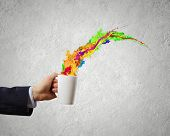 Close up of businessman holding white cup with splashes flying out