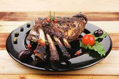 grilled ribs on wooden table with pomegranate seeds