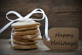 image of ginger bread  - Ginger Bread Cookies with white Ribbon and Label with Happy Holidays on it on wooden Background - JPG