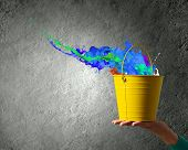 Close up of woman hand holding bucket with colorful splashes