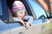 Happy little girl in striped hat looking out car window