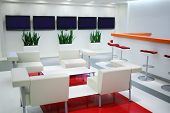 Empty waiting area with white chairs and plasma screens in office
