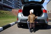 Little boy in white hat standing with machine number and socket wrench near open trunk of car
