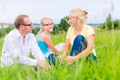 Parents and daughter sitting on grass of lawn or field