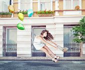 Balloons fly with young beautiful girl. Creative concept