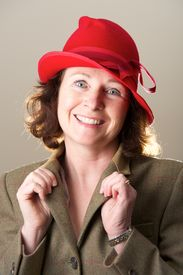 foto of lapel  - Brunette in red hat holding jacket lapels - JPG