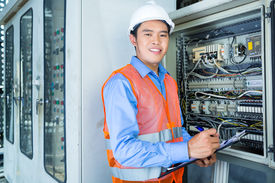 stock photo of breaker  - Asian Indonesian Technician or electrician making function test on breaker box or switchbox with power lines on construction site or in factory for acceptance - JPG