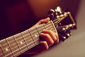picture of guitar  - Color detail of hand playing of an old acoustic guitar.