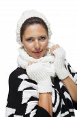 stock photo of snuggle  - Attractive elegant woman in winter fashion snuggling down into her white scarf and black and white jumper to ward off the cold winter weather on white - JPG