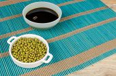 picture of soy sauce  - Bowl with soy sauce and soy beans on a bamboo mat