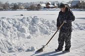 picture of snow shovel  - A man in camouflage clothing removes snow shovel - JPG