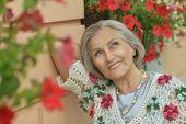 image of beautiful senior woman  - Portrait of a beautiful senior woman in green park - JPG
