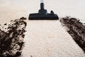 stock photo of carpet  - Photo Of Vacuum Cleaner Cleaning Dirt On Carpet - JPG