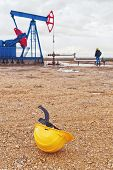 image of oil derrick  - Protective Industrial Safety Helmet and Pumpjack Oil Pump operating on natural gas in the field pumping from the oil well - JPG