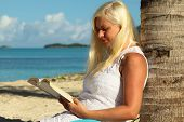 picture of palm-reading  - blonde woman sitting by palm tree and reading a book - JPG