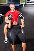 pic of personal trainer  - A shot of a male personal trainer assisting a woman lifting weights - JPG