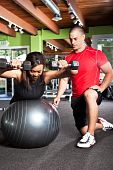picture of personal trainer  - A shot of a male personal trainer assisting a woman lifting weights - JPG