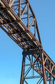 picture of girder  - Section of Rusty Steel Girder Railroad Bridge in Bright Daylight with Clear Blue Sky Background - JPG