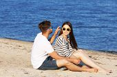 picture of couple sitting beach  - Young couple sitting on beach - JPG