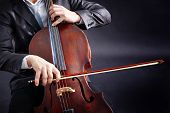 stock photo of cello  - Man playing on cello on dark background - JPG