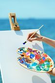 stock photo of paint palette  - Female hand holding palette with paints and easel with canvas on beach - JPG