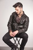stock photo of down jacket  - Side view of a handsome young fashion man sitting on a chair while looking down - JPG
