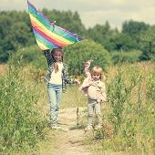 picture of kites  - little cute girls flying a kite in a meadow on a sunny day - JPG