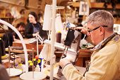 stock photo of stitches  - Shoemaker stitching leather in a workshop - JPG