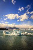 stock photo of iceberg  - Icebergs floating in Jokulsarlon Lagoon by the southern coast of Iceland - JPG