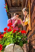 stock photo of adultery  - Couple in love at mountain hut window wearing traditional clothing - JPG