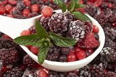 pic of berries  - White porcelain bowl with frozen berries and mint leaves stands in the midst of other berry fruits - JPG