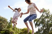 stock photo of bouncing  - Mother And Daughter Bouncing On Trampoline Together - JPG