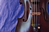 picture of violin  - Closeup of violin against a blue linen background - JPG