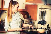 foto of stir fry  - Woman in kitchen cooking stir fry frozen vegetables - JPG