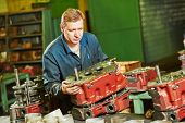 picture of assemblage  - industrial worker assembler with gearbox units at manufacture workshop - JPG