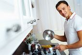 pic of saucepan  - Young man with saucepan going to cook spaghetti  - JPG