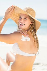 pic of sun tan lotion  - Pretty blonde woman spreading sun tan lotion on her shoulder at the beach - JPG