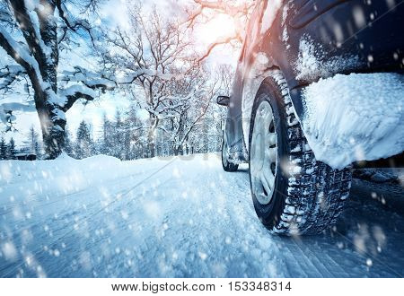 poster of Car tires on winter road covered with snow. Vehicle on snowy alley in the morning at snowfall