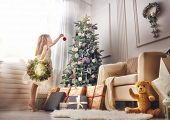 Merry Christmas and Happy Holidays!  Cute little child girl is decorating the Christmas tree indoors poster