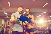 fitness, sport, exercising and diet concept - smiling young woman and personal trainer with clipboar poster