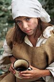 stock photo of emaciated  - Poor little beggar girl with a vintage mug in her hand - JPG