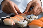 Closeup of chef hands preparing japanese food. Japanese chef making sushi at restaurant. Young chef  poster