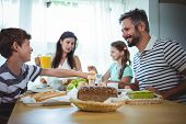 Happy family having breakfast at home poster
