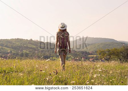 poster of Girl in vacation. Summer vacation. Traveler girl walking through fields. Young girl traveler walking in nature. Traveler with backpack in nature. Girl traveler walk through nature in summer day. Traveler. Summer. Backpack. Girl. Walk. Nature. Vacation. Li